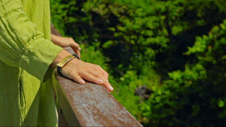 A young European girl stands in the summer on a balcony holding her hand to a wooden railing in a green dress Banco de Imagens