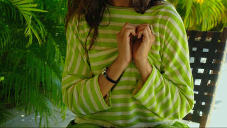 A young girl in a green dress with made a heart with her hand sitting on a bench in the backyard with green plants on the background Banco de Imagens