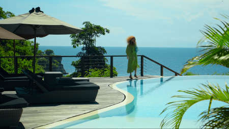 Young long red curves hair girl walking in the backyard with a green garden, pool with blue clean water and blue sky in a beautiful long green dress Banco de Imagens