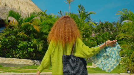 A young girl with red hair going on a grass in the backyard with a green garden in a beautiful long green dress