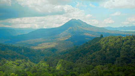 View of the volcano Batur in Indonesia with green trees and high cloud Banco de Imagens