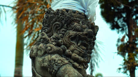 An old Indonesian ethnic stone statue of an evil demon with an open mouth and fangs covered with cloth during the day Banco de Imagens