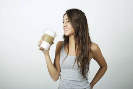 disposable cup: Attractive young woman drinking coffee out of a disposable cup.