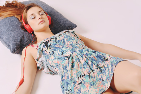 lying down on floor: Young girl lying on the floor with red headphones Stock Photo