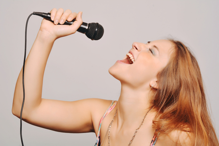 cantando: Mujer rubia hermosa que canta con el micr�fono. Concepto de la m�sica