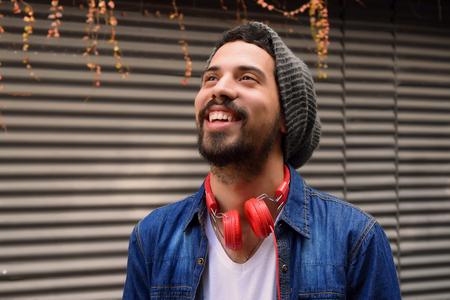 estilo urbano: Retrato de hombre joven con auriculares rojos.