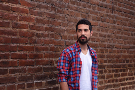 cool boys: Portrait of young latin man against a brick wall. Stock Photo