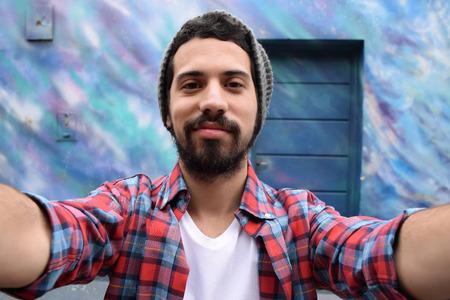 carita feliz: Hombre latino joven que toma una selfie. Concepto de la tecnolog�a.