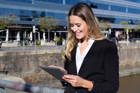 succesful woman: Succesful business woman working on a tablet outside her office.
