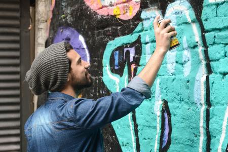 dessin: Jeune peintre latin urbaine dessiner un graffiti sur le mur. Banque d'images