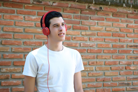 estilo urbano: Young latin man with red headphones. Trendy and urban style. Foto de archivo