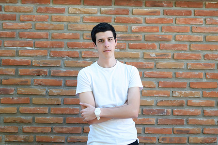 stylish man: Portrait of young latin man against a brick wall. Teenager posing. Stock Photo