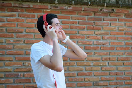 stylish man: Young latin man with red headphones. Trendy and urban style. Stock Photo