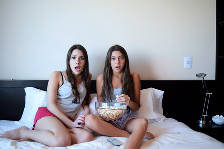 personas viendo television: Dos hermosas mujeres j�venes en la cama viendo una pel�cula o la televisi�n y comiendo palomitas y nachos. Expresi�n asustada.
