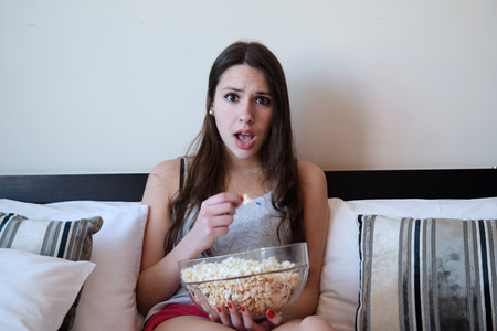 personas viendo television: Latina woman watching a movie in her bed, while eating popcorn. Surprised expression. Foto de archivo