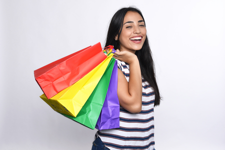 compras compulsivas: Young latin Woman with shopping bags. Isolated over white background