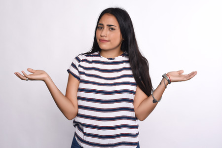indecisive: Indecisive young woman with arms open. Isolated white background. Stock Photo