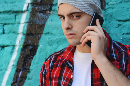 latinamerican: Portrait of young handsome man talking on the phone outdoors