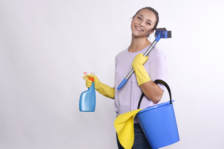Portrait of young woman holding cleaning products. Isolated on white background.