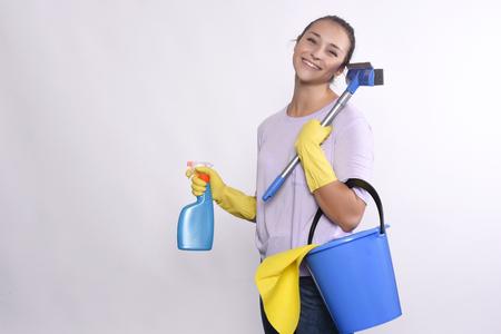 casalinga: Ritratto di giovane donna azienda prodotti per la pulizia. Isolato su sfondo bianco.