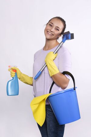 productos de limpieza: Portrait of attractive young woman with cleaning products, protective gloves and bucket. Isolated white background.