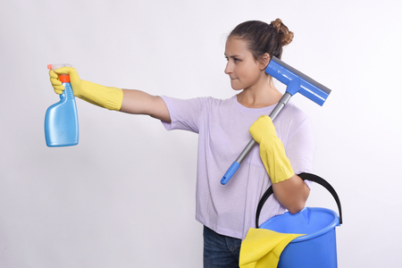 productos de limpieza: Portrait of attractive young woman with cleaning products, gloves and bucket. Isolated white background.