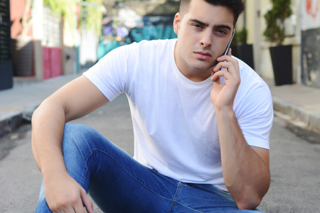 celphone: Portrait of young handsome man talking on the phone outdoors
