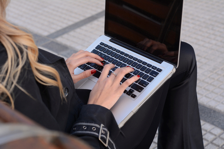 succesful woman: Succesful business woman working on a laptop outside her office.
