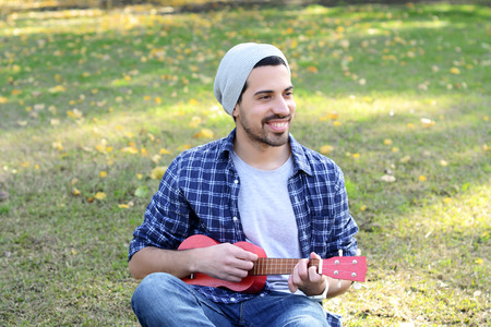 ukelele: Portrait of young handsome man playing the ukelele in a park. Outdoors.