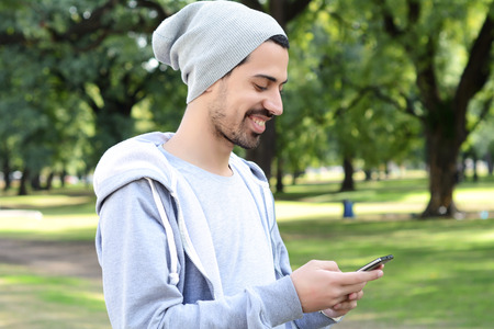 celphone: Portrait of young latin man using his smartphone. Outdoors.