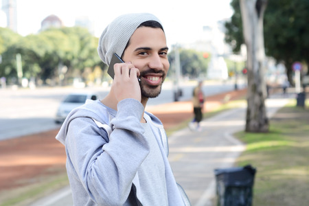celphone: Portrait of young latin man talking on the phone. Outdoors.
