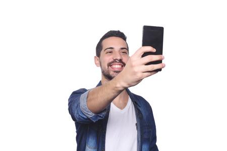 Portret van aantrekkelijke jonge man die een selfie met zijn smartphone. Geïsoleerde witte achtergrond. Stockfoto
