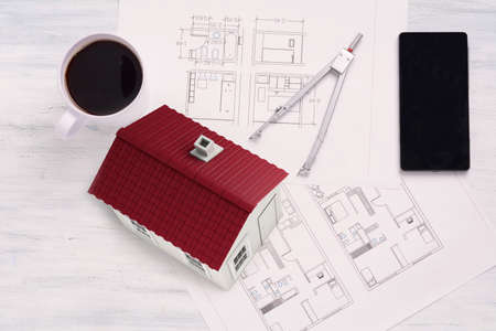 housing project: House with house plan, coffee and smartphone. Architecture concept.