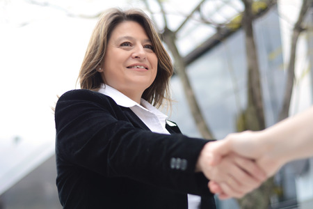 deal making: Close up of business woman hand shaking for making a deal. Outdoors. Stock Photo