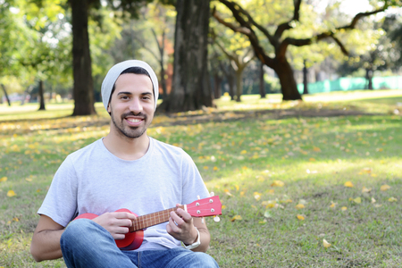 Portrait of young handsome man playing the ukelele in a park. Outdoors.