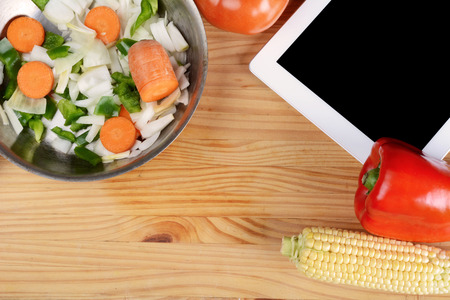 Vegetables with a digital tablet pc on wooden table. Healthy food concept.