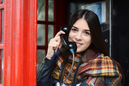 Portrait of young beautiful woman talking on phone in red box telephone. Tourism concept. Outdoors. Stock Photo