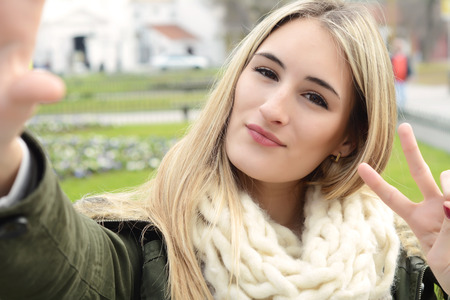Portrait of a young beautiful woman taking selfie. Outdoors.