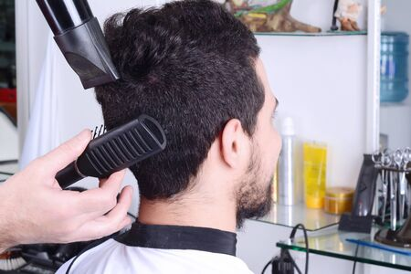 Close up of young man in hairdressing and drying his hair with a hairdryer.