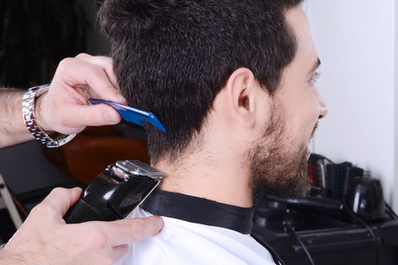 haircutter: Close up of young man having a haircut with hair clippers. Stock Photo