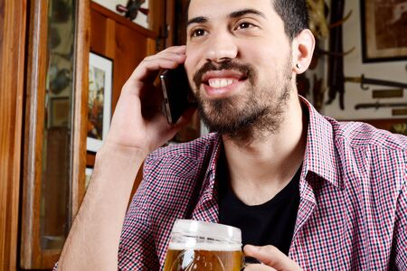 Portrait of young latin man talking on the phone with glass of beer and snacks in a bar. Indoors.