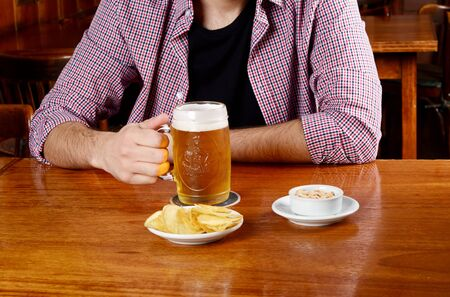 Portrait of young latin man drinking beer and eating snacks at a bar. Indoors.
