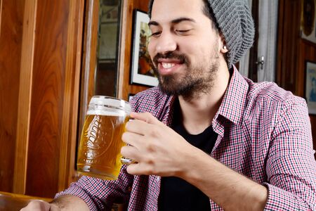 Portrait of young latin man drinking beer at a bar. Indoors.