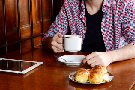 Close up of a man with digital tablet and drinking coffee at a cafe. Indoors. Stock Photo