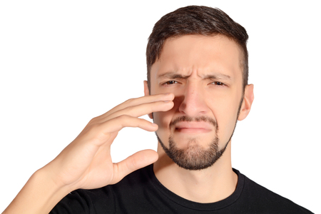 intolerable: Portrait of young man holding his nose against a bad smell. Isolated white background.