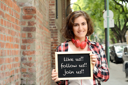 Young beautiful woman holding chalkboard with text Like us, follow us, join us. Social media concept. Outdoors.