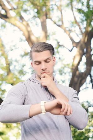 Portrait of young latin man looking at his watch at park. Outdoors.