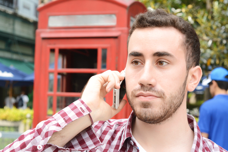 celphone: Portrait of young latin man talking on the phone. Outdoors. Urban scene. Stock Photo