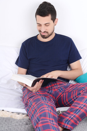 Attractive young man relaxed in bed and reading a book. Indoors.