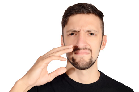 Portrait of young man holding his nose against a bad smell. Isolated white background.